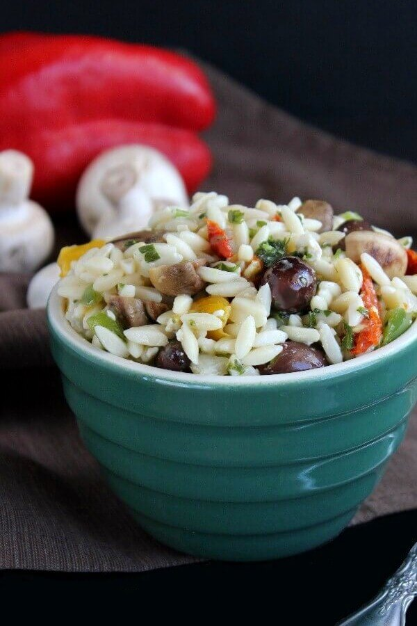 Greek Orzo Pasta Salad is piled high in a green bowl and is set against a black background. Fresh Red bell peppers and mushrooms are on the black cloth too.