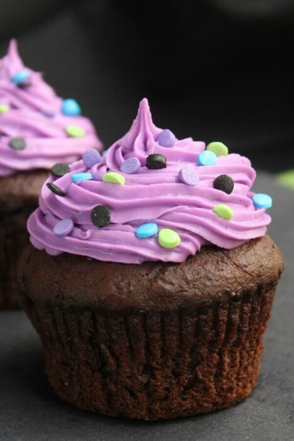 Halloween Chocolate Lava Cupcakes are dressed up for October. Chocolate cupcakes with a electric purple swirled frosting and sprinkled with Halloween colors for the festivity.