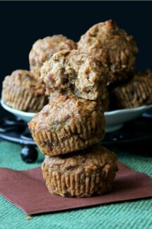 Hawaiian Banana Date Muffins are stacked three high with the top muffin torn in half to show the delicious inside ingredients. Sitting on a chocolate colored napkin and a green woven mat.
