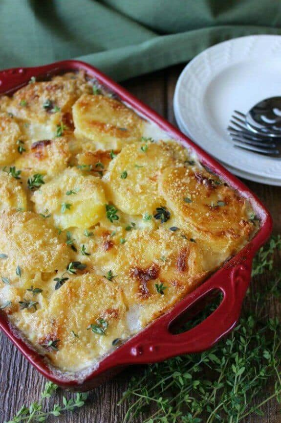 Dairy Free Herbed Scalloped Potatoes is tilted towards you and is golden brown and in a red casserole dish. Fresh herbs and green cloth on the side.