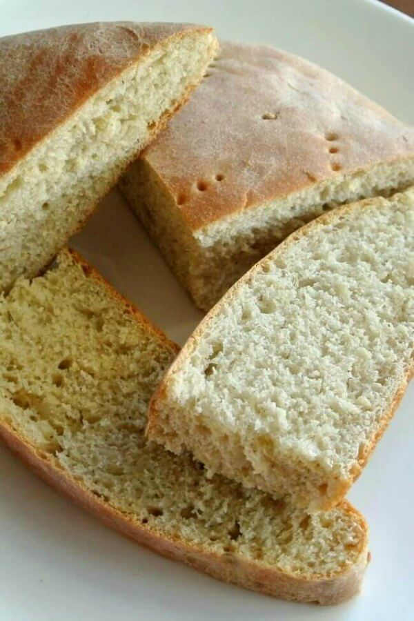 Sage Dill Bread is sliced into half pieces and they are lying every which way on top of each other.