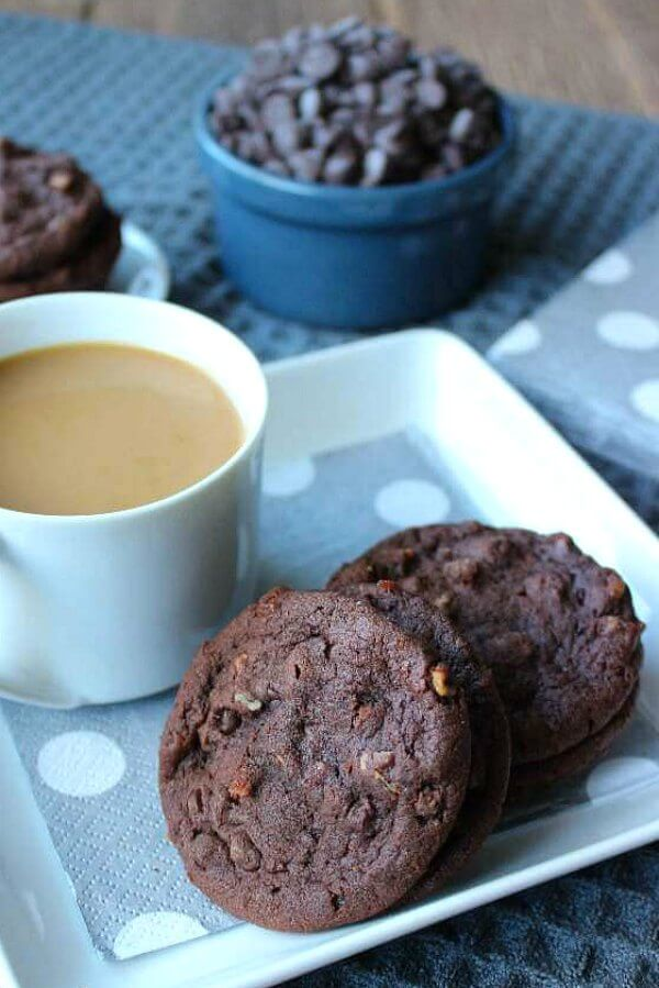 Irish Cream Chocolate Cookies are sitting on a square white plate with a cup of coffee in a white cup. Silver and silvery blue colors in the cloth and napkins.