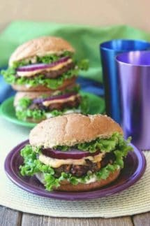 Kidney and Black Bean Burgers are on a big bun with layers rippled lettuce, patty creamy orange sauce, a big fat red onion slice and more. All on a purple plate.