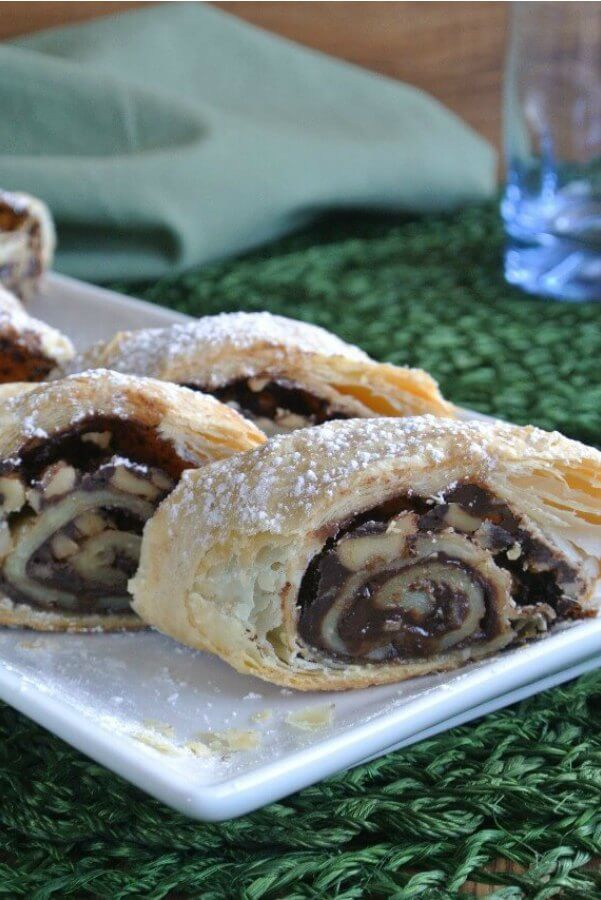 Mother's Chocolate Strudel is sliced with chocolate and walnuts showing in the rolled layers of a flaky crust. All served on a white plate.