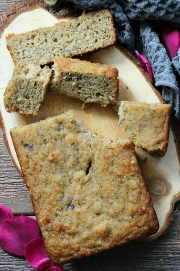 Moist Gluten-Free Banana Bread is an overhead photo of golden brown banana bread with a couple of slices laying out for your view with the loaf. All on a slab of a wooden trivet.