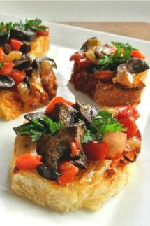 Mushroom Bruschetta Crostini is a mix of mushrooms, onions and red bells. The mix is piled high on small toasts and plated on a white square plate.