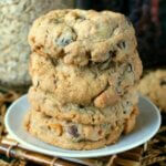 Nut Free Oatmeal Chocolate Chip Cookies are stacked 4 high and sit in small white plates sitting a an open weave beige mat.