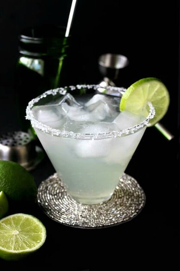 Silver Cadillac Margarita is a simple cocktail that is pale lime green and is pour in a flared glass with ice cubes. A thin lime slice is on the glass edge against a black surrounding.