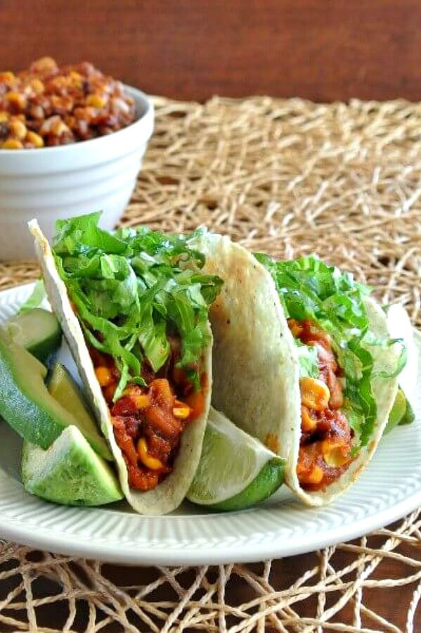 Slow Cooker Chipotle Tacos are sitting on an ivory pottery plate. The two tacos are facing us so that the spicy pinto beans and corn mix are showing with avocado on the side.