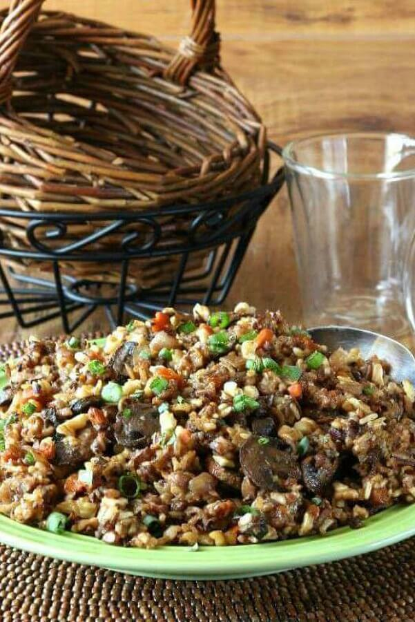 Slow Cooker Wild Rice Recipe with Pecans is piled high on a green plate and showing all of the glistening ingredients. Sitting on a wooden breaded mat.