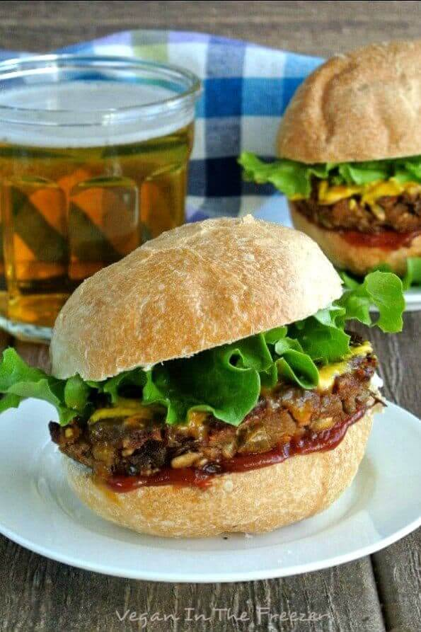 Green Lentil Burger patty is between a bun and is layered with lettuce and condiments with a beer sitting behind.
