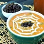 Spicy Pumpkin Black Bean Soupis in a green bowl and has a cream spider web drawn in the top. Black beans are dotted in the center. Great Halloween visual.