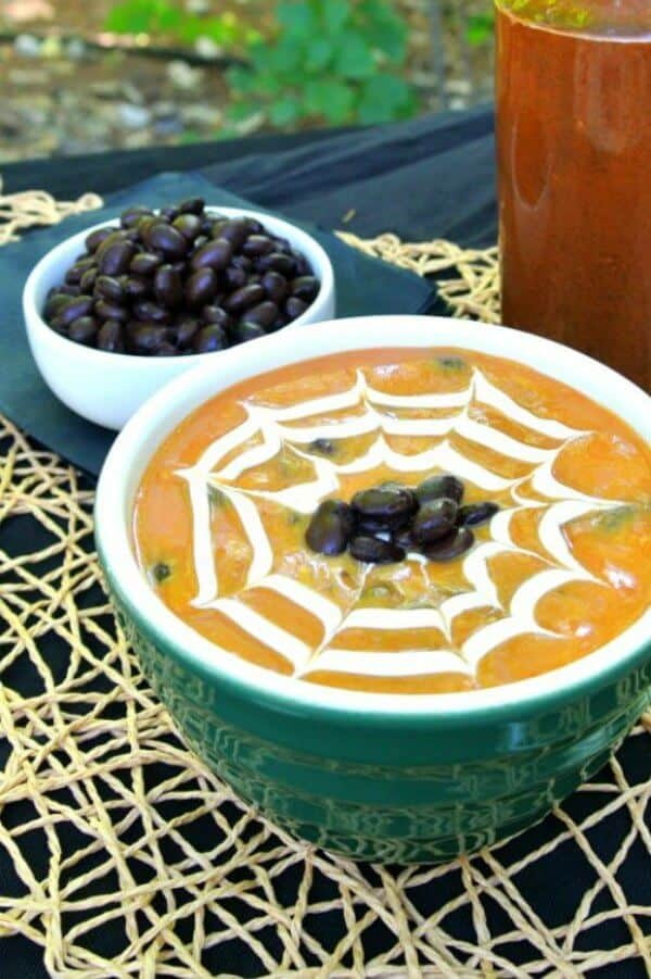 Spicy Vegan Pumpkin Soup with black beans is in a green bowl and has a cream spider web drawn in the top. Black beans are dotted in the center. Great Halloween visual.