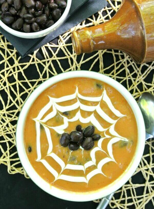 Spicy Vegan Pumpkin Soup with black beans is an overhead photo looking down at rich pumpkin soup with a cream spider web drawn in the top. Black beans are dotted in the center. Great Halloween visual.