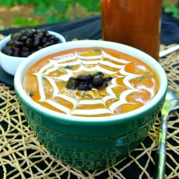 Spicy Pumpkin Black Bean Soup is in a green bowl and has a cream spider web drawn in the top. Black beans are dotted in the center. Open-weave golden mat for more spidery ideas.