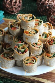 Spicy Tortilla Rollups are in a close-up photo and are rolled up with layers of spicy pesto baby spinach and so much more. Rolled tight and pierced with a toothpick.