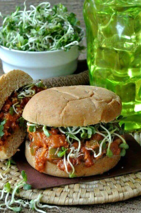 Vegan BBQ Chicken Sandwich is overflowing a big fat whole wheat bun. Sitting on a brown napkin and a woven round mat. Sprouts are inside the sandwich too with a big bowl behind the sandwich.