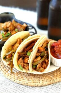 Vegan Fajitas with Meatless Chicken have tortillas lined up on a plate with the tops open and the veggies and meatless chicken piled high. Salsa on the side.