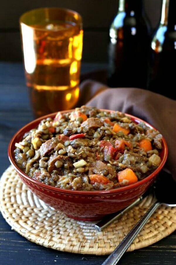 Vegan Lentil Sausage Casserole is piled high in a red porcelain bowl and sitting on a woven mat. A gold glass filled with beer sits behind.