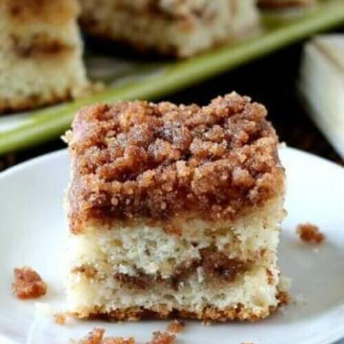 Vegan Pumpkin Spice Cinnamon Cake is vut into a square and is sitting on two small white plates waiting for one to be picked up. The cake shows the layers of cinnamon streusel.
