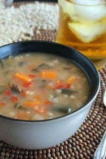 Vegetable Barley Soup is a side view of the rich brothy soup showing carrots, barley, tomatoes, spinach, and more. Beige bowl with a black interior on a dark brown wooden beaded mat.