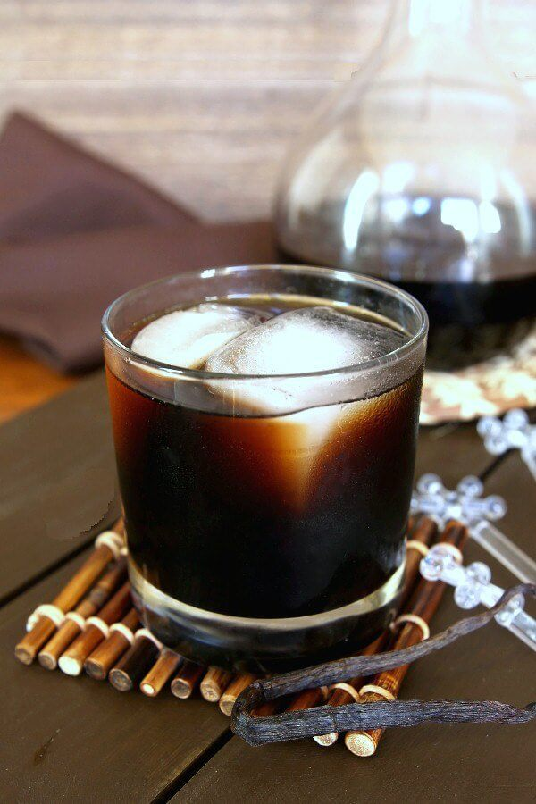 Homemade Kahlua is poured into a glass and has two giant ice cubes. Sitting on a bamboo stick coaster in front of a decanter with more Kahlua and clear snowflake topped swizzle sticks on the side.