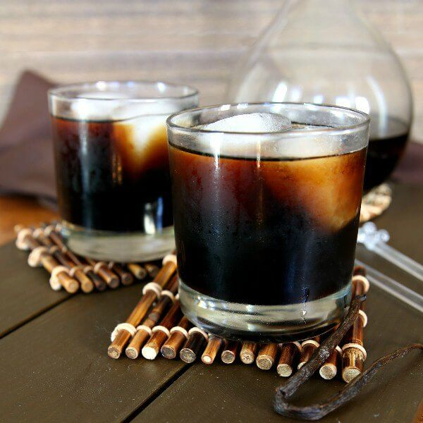 Homemade Kahlua is poured into two glasses and are filled with two giant ice cubes. Sitting on bamboo stick coasters in front of a decanter with more Kahlua and a vanilla bean in front.