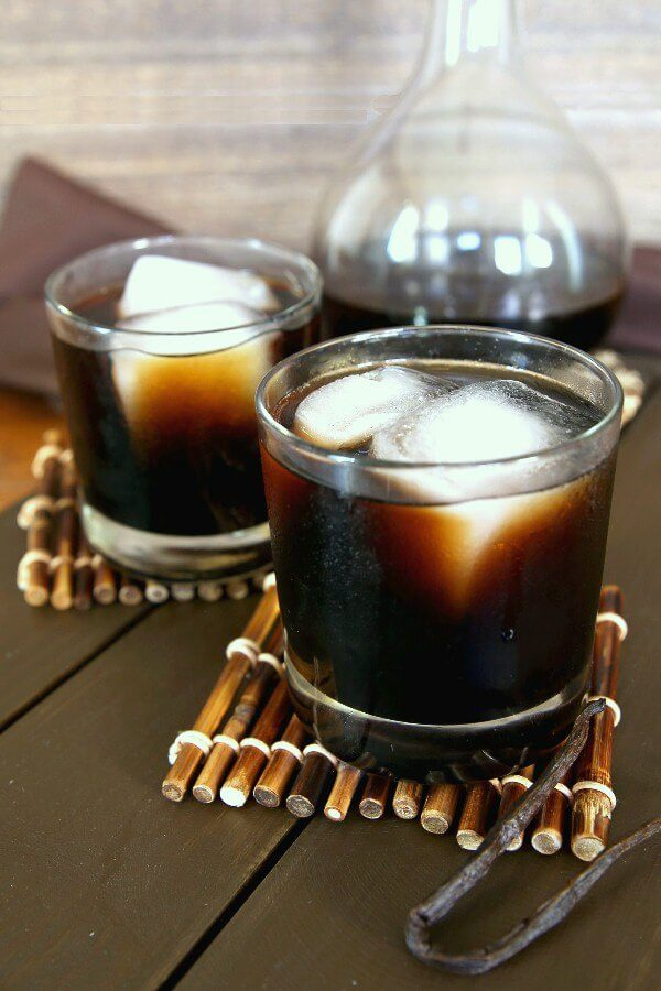 Homemade Kahlua is poured into two glasses and are filled with two giant ice cubes. Sitting on a bamboo stick coaster with a vanilla bean on the side.