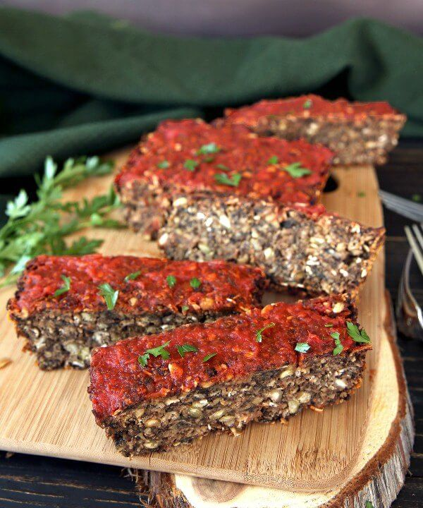 Vegan Meatloaf with Chickpeas, Green Split Peas and Mushrooms is sitting on a breadboard and tilted forward with half of the loaf sliced. It's also topped with marinara sauce and sprinkled with fresh herbs.