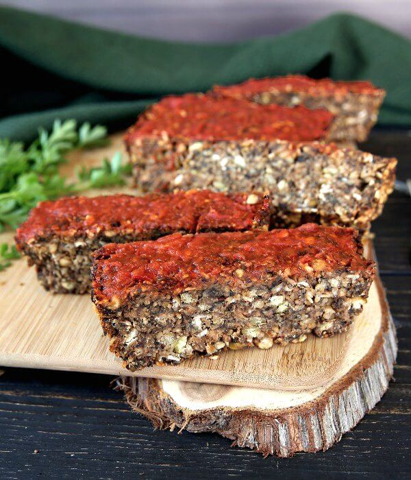 Vegan Meatloaf with Chickpeas, Green Split Peas and Mushrooms is sitting on a breadboard with an almost straight on view. Marinara sauce topped sliced are all set at an angle to show the texture of the veggie loaf.