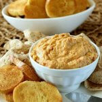 Artichoke Chipotle Hummus is golden in color and is heaped in a white bowl. It's sitting on a white plate with crostini toasts sitting around.