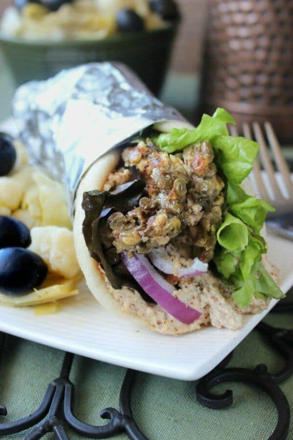 Lentil Panini Burgers are rolled into a pita flatbread and are sitting on a white square plate with olives, onions and lettuce peeking out.