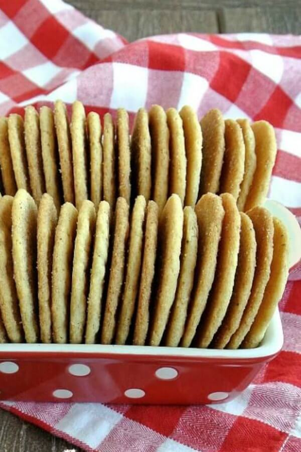 Cinnamon Sugar Cookies are stacked back to front on there side in a red and white polka dot bowl and it all sits on a red and white checkered cloth.