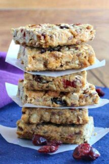 Cranberry Date Breakfast Bars are stacked sic high and divided by parchment squares every two bars. Sitting on a blue mat with a purple napkin.