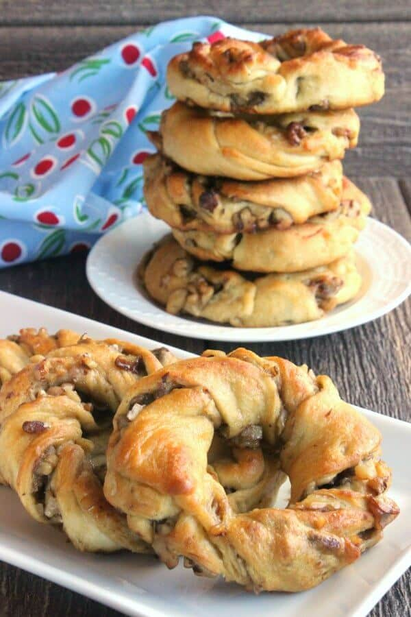 Crescent Roll Breakfast Rings are sprawled across a rectangle white plate on a rough wood table top. A stack of 5 more are stacked high on a plate behind.