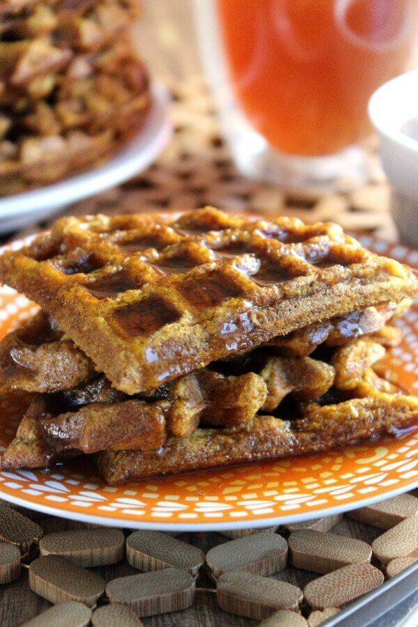 Vegan Pumpkin Waffles are cut into triangles and stacked high on an orange and white patterned plate. Maple syrup is filling the crannies and overflowing intro the plate.