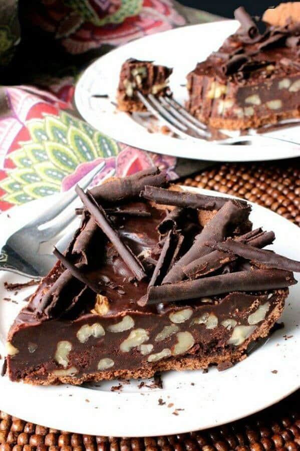 Easy as Chocolate Pie is sliced into a big piece and it sitting on a white pate. Walnuts are visible inside and chocolate curls are on top.
