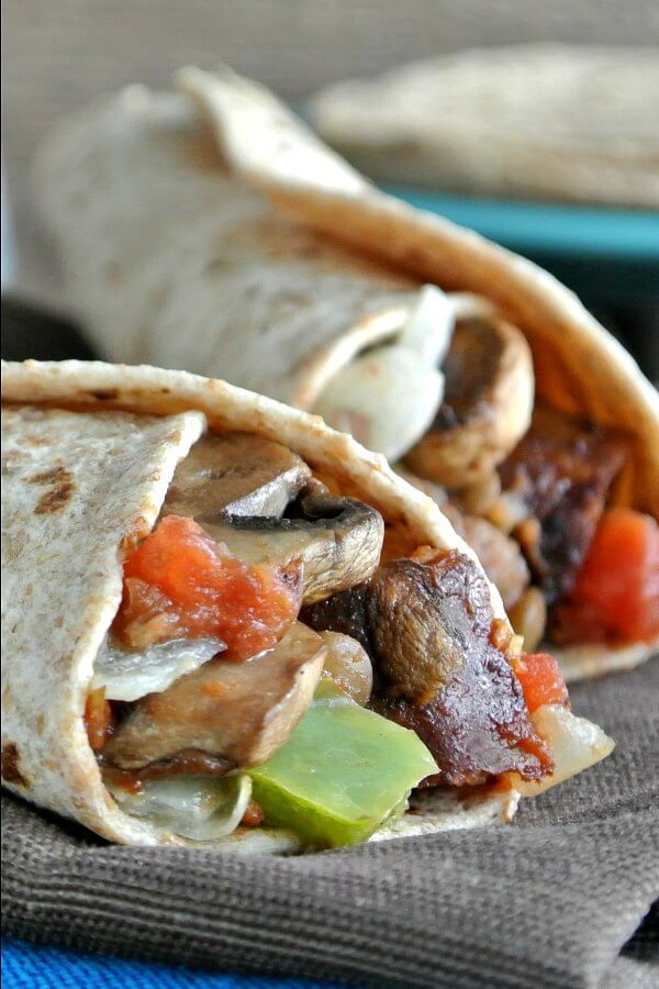 Healthy Breakfast Burrito is overflowing with veggies and plant-based sausage. Two burritos are laying next to each other on a brown cloth napkin.