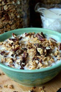 Homemade Date Bar Granola is in a green pottery bowl with a bit of dairy-free milk floating in and out of the granola.