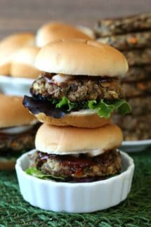 Lentil Burger Sliders are stacked two high in a white scalloped dish. All are sitting on a green mat. Lots of condiments peeking out of the sliders.