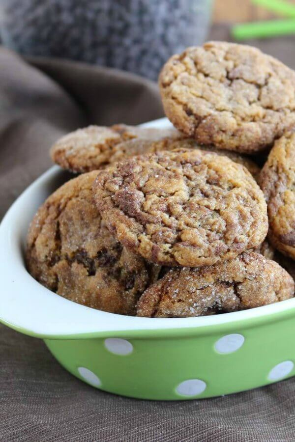 Marbled Peanut Butter Chocolate Cookies are piled high in a green and white polka dot bowl. All the brown shades of peanut butter and chocolate are showing.