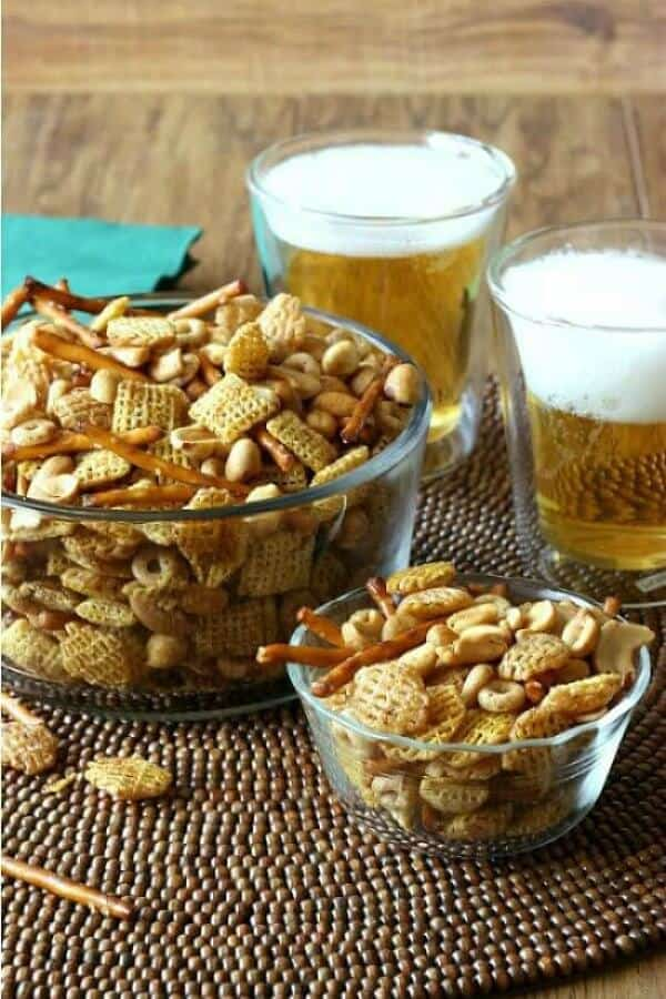 Nuts and Bolts Party Mix are filling two glass bowls to overflowing with two foam topped beers sting behind.