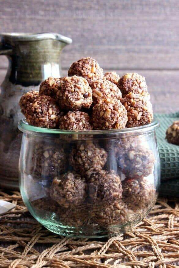 Chocolate Peppermint Cookie Dough is filling a large round jar and then is piled as high as it can. The jar is sitting on an open weave mat against a green cloth towel.