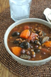 Slow Cooker Lentil Vegetable Soup is filling a gray bowl and show a rich brown broth with carrots, lentils, mushrooms, barley, tomatoes and more. On a brown beaded mat.