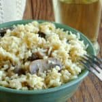 Slow Cooker Mushrooms and Rice is served in a green pottery bow' with contrasting mushrooms sticking out of the rice. Ivory cloth behind and a glass of chardonnay.