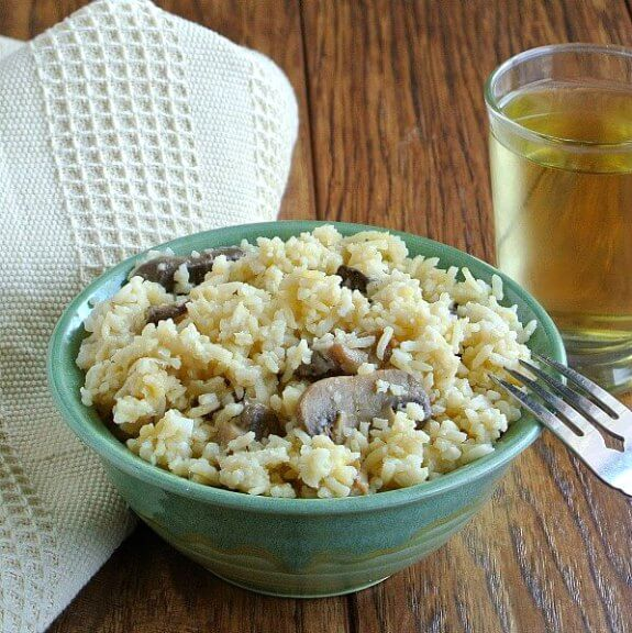 Healthy Slow Cooker Mushrooms and Rice is served in a green pottery bowl with contrasting mushrooms sticking out of the rice. Titled forward with a fork leaning on the rim and a glass of chardonnay behind.