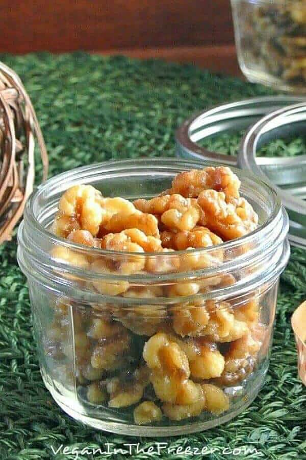 Slow Cooker Maple Glazed Walnuts are in a pint jar with the lid off and a festive ribbon laying the side green woven mat.