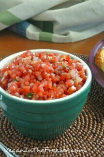 Tomato Bruschetta is a gorgeous red color in a small white rimmed green bowl. Sitting on a chocolate colored beaded mat with golden crostini toasts to the side.