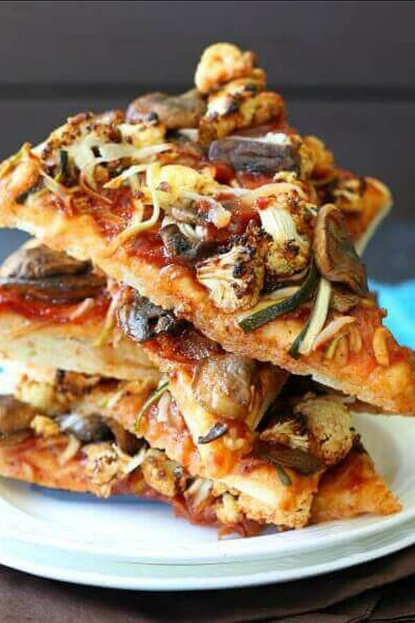 Vegan BBQ Veggie Pizza is stacked five slices high at all angles with glistening veggies showing throughout.