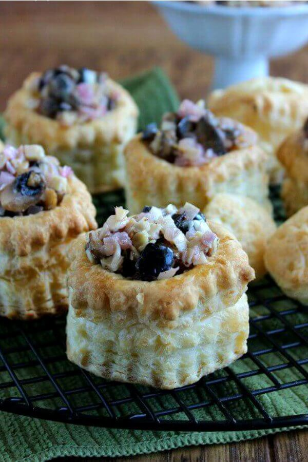 Vegan Puff Pastry Appetizer is photographed with filled pastried lined up on a black cooling rack. They are sitting on a green mat.